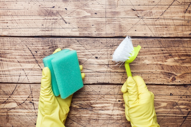 Hand im gelben handschuh und im reinigungsschwamm für das säubern auf hölzernen hintergrund.