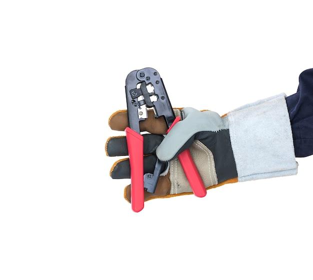 Hand im handschuh, der abisolierzange auf weiß hält