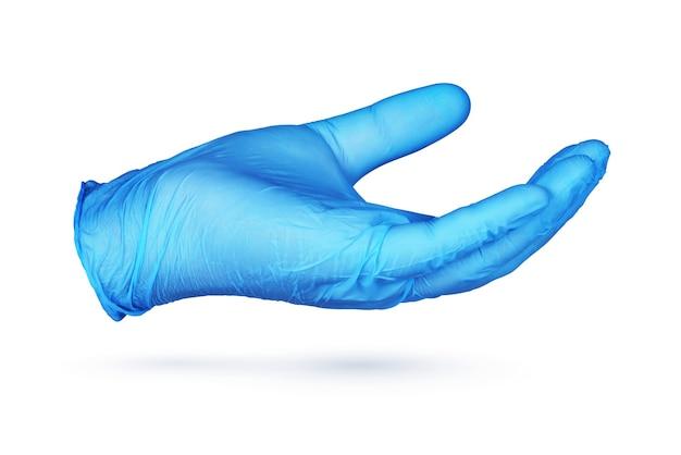 Hand in blauem nitril-schutzhandschuh, der etwas auf weißem hintergrund hält oder zeigt.