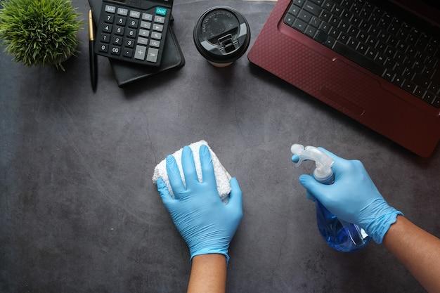 Hand in blauen gummihandschuhen, die sprühflaschenreinigungsbürotisch halten