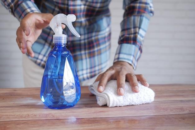 Hand in blauen gummihandschuhen mit sprühflaschen-reinigungstisch