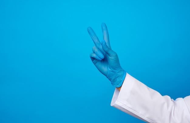 Hand in blauen sterilen medizinischen handschuhen zeigt siegesgeste, konzept des sieges über die krankheit