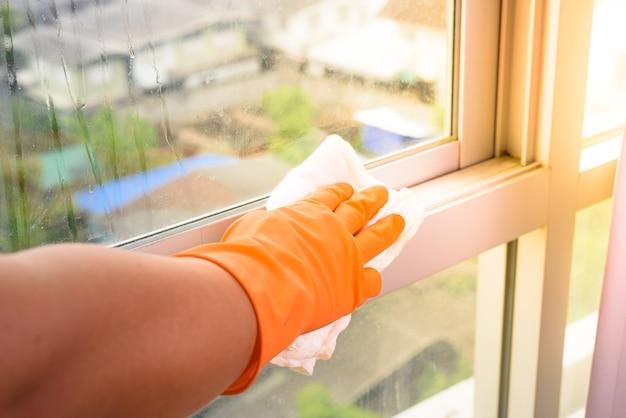 Hand in den handschuhen, die zu hause fenster mit lappen- und reinigungsmittelspray säubern. hausarbeit