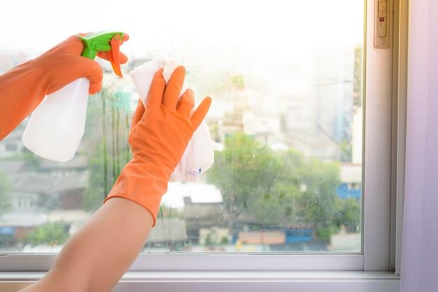 Hand in den handschuhen, die zu hause fenster mit lappen- und reinigungsmittelspray säubern.