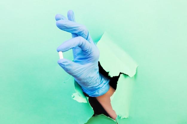 Hand in einem blauen medizinischen handschuh mit einer weißen tablette. durch ein loch im grünbuch. medizin, pharmazie, gesundheit. minimalismus, .