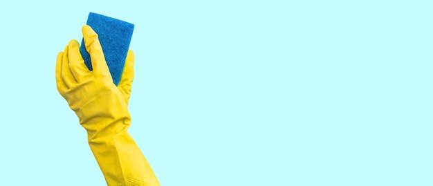 Hand in einem gelben gummihandschuh mit einem reinigungsschwamm isoliert auf hellem hintergrund, küchenreinigungskonzept foto