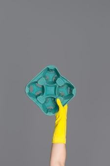 Hand in einem gelben gummihandschuh zum reinigen hält eine grüne pappe