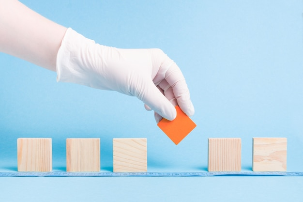 Hand in einem gummi einweg weißen medizinischen handschuh nimmt einen roten block ein holzquadrat, dominosteine sind aufgereiht, blaue oberfläche