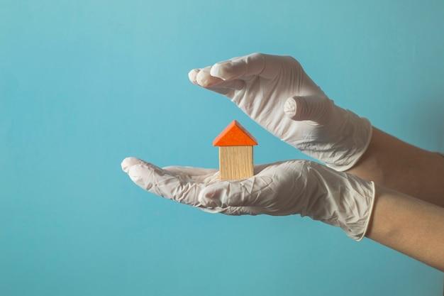 Hand in einem handschuh hält ein holzhaus - konzept der krankenversicherung oder des hausarztes