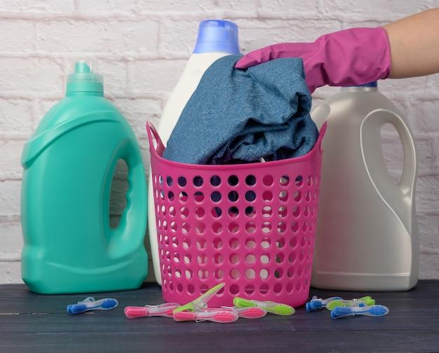 Hand in einem rosa handschuh legt dinge in einen plastikwäschekorb gegen eine weiße backsteinmaueroberfläche