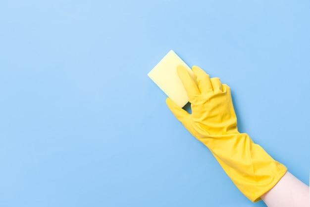 Hand in einen gelben gummihandschuh hält einen gelben schwamm zum abwaschen und reinigen