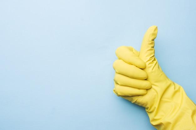 Hand in gelben handschuhen für die reinigung auf blauem hintergrund.