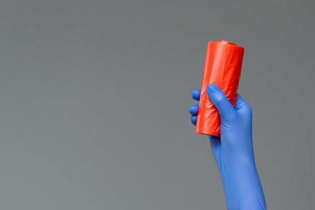 Hand in gummihandschuh hält farbigen müllsack