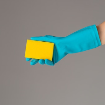 Hand in gummihandschuh hält farbwaschschwamm