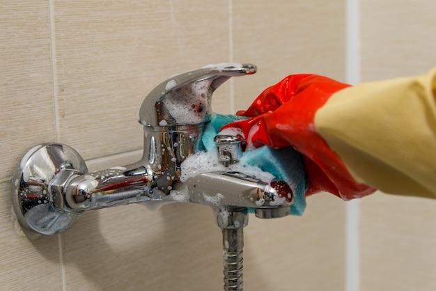 Hand in gummihandschuh reinigt schmutzigen verkalkten duschmischerhahn, nahaufnahme foto