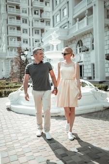 Hand in hand. liebevolles ehepaar, das händchen hält und sich ansieht und gemeinsam einen spaziergang durch die stadt macht.