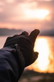 Hand in handschuh in die sonne zeigen