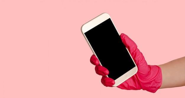 Hand in handschuhen, die smartphone mit modell auf rosa raum halten. kontaktloses einkaufen und liefern.