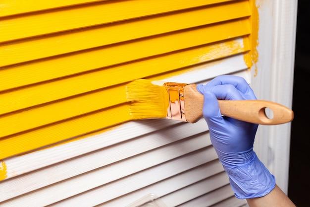 Hand in lila gummihandschuh mit pinsel, der natürliche holztür mit gelber farbe malt