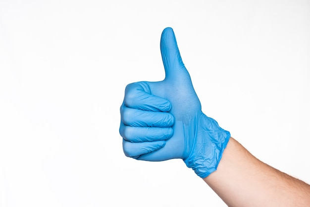 Hand in medical blue latex handschuh daumen hoch zeichen. mögen. weißer hintergrund. schutzkonzept
