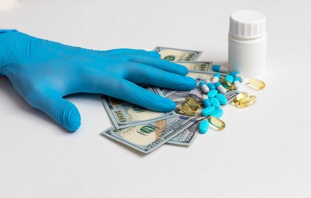 Hand in medizinischem handschuh auf us-dollar und pillen und glas mit pillengeld- und medizinkonzept