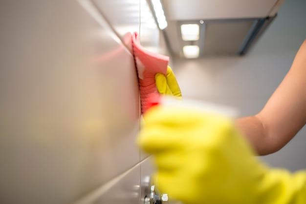 Hand in rosa schutzhandschuh reinigung fliesen mit lappen. frühe frühjahrsreinigung oder regelmäßige reinigung. reinigungsmann reinigt haus.