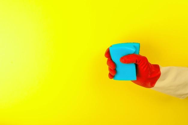 Hand in rotem handschuh, der einen schwamm hält