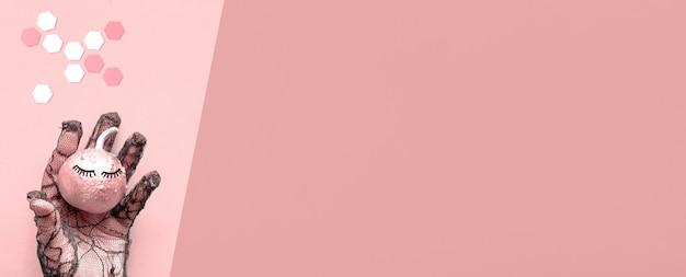 Hand in schwarzem netzhandschuh, der rosa kürbis mit geschlossenen augen hält. kreative halloween-panorama-wohnung lag auf rosa papierwand mit kopierraum