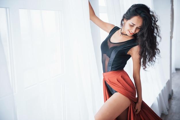 Hand ist auf vorhängen. schöne tänzerin in der schwarzen und roten kleidung, die im weißen raum nahe fenster übt