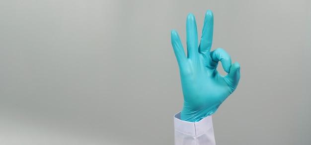 Hand ist ein ok-handzeichen und trägt ein arztkleid und einen blauen medizinischen handschuh auf grauem hintergrund. studioaufnahmen.