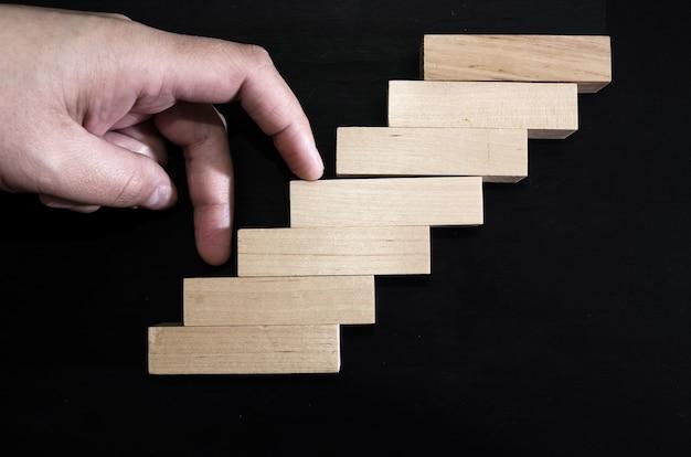 Hand klettert treppen mit holzklötzen auf schwarz
