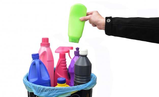 Hand legen sie eine plastikflasche in einen papierkorb