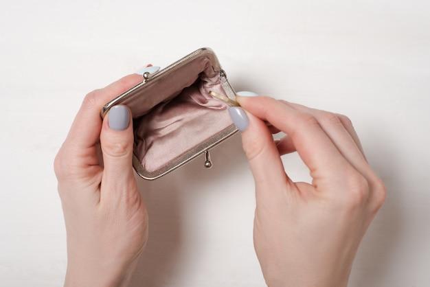 Hand legt eine münze in einen leeren offenen metallgeldbeutel