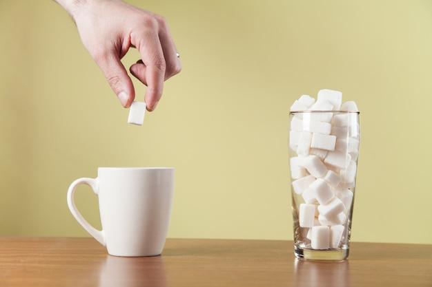 Hand legt zuckerwürfel auf kaffeetasse.