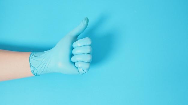 Hand macht ein ok handzeichen und trägt chirurgische handschuhe auf blauem hintergrund.