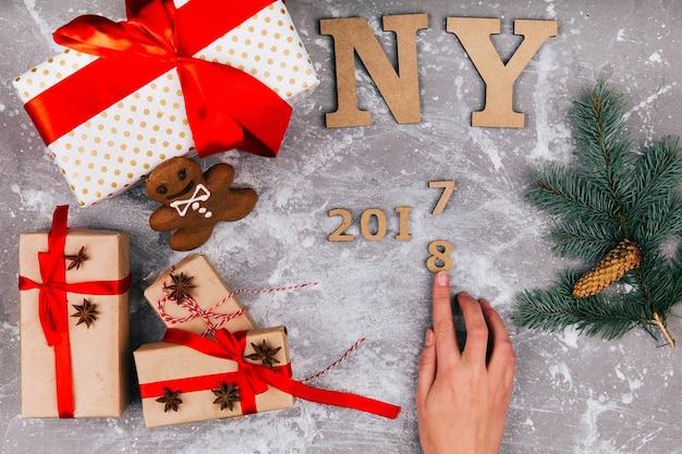 Hand macht nummer 2017 bis 2018 auf grauem boden, der mit weihnachtsgeschenkkästen bedeckt wird