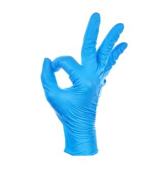 Hand macht okay, trägt ein blaues medizinisches nitrilhandschuhsymbol.