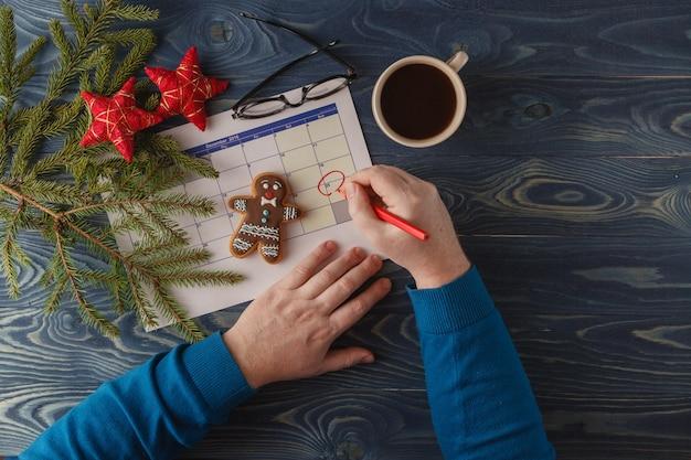 Hand markieren sie weihnachtsdatum auf einem kalender