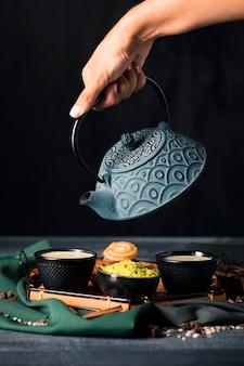 Hand mit auslaufendem getränk der teekanne in der schale