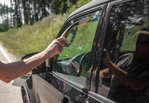Hand mit autogummiwischer, der im sommer autofenster im freien säubert