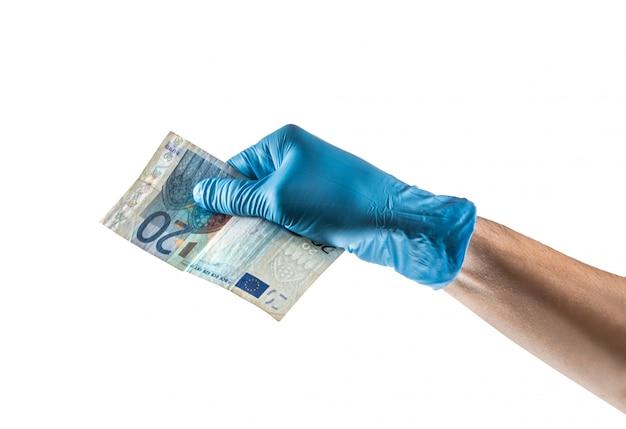 Hand mit blauem latexhandschuh, der eine 20-euro-rechnung hält