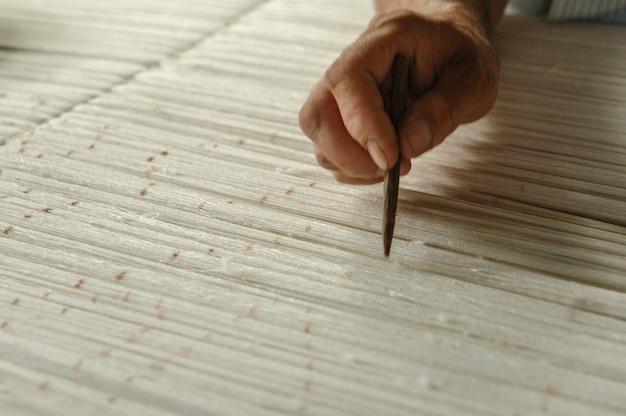 Hand mit bleistift macht markierungen auf dem teppich weben und herstellung von handgefertigten teppichen nahaufnahme