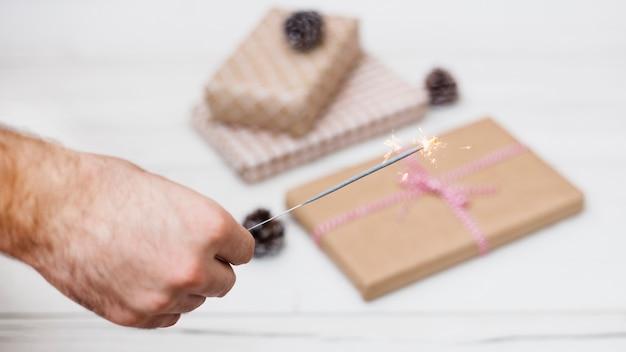 Hand mit brennendem bengallicht in der nähe von geschenkboxen in verpackungen und schmuckstücken