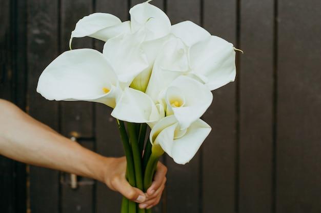 Hand mit calla lilien blumen auf einem dunklen holz