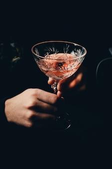 Hand mit dem alkoholcocktail, das den toast lokalisiert auf einem schwarzen hintergrund macht