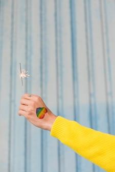 Hand mit dem gezogenen regenbogenherzen, das brennende wunderkerze hält