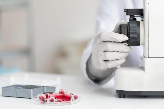 Hand mit dem mikroskop schließen
