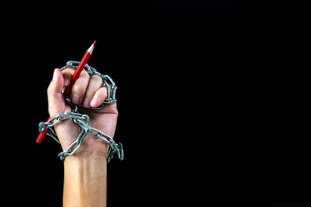 Hand mit dem roten bleistift gebunden mit fesseln
