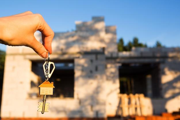 Hand mit dem schlüssel zum zukünftigen haus vor dem hintergrund einer baustelle und wände aus porösem betonblock. ein haus bauen, in ein neues häuschen ziehen, auf dem land bewirtschaften