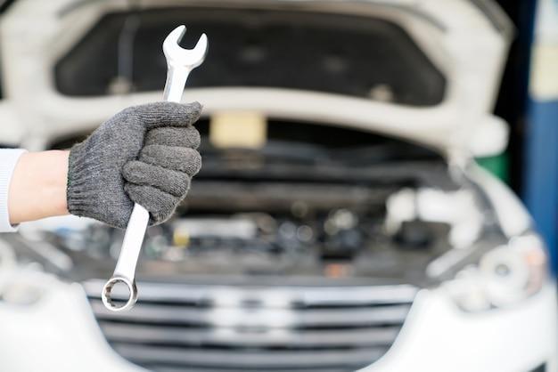Hand mit dem schraubenschlüssel in der reparaturwerkstatt.